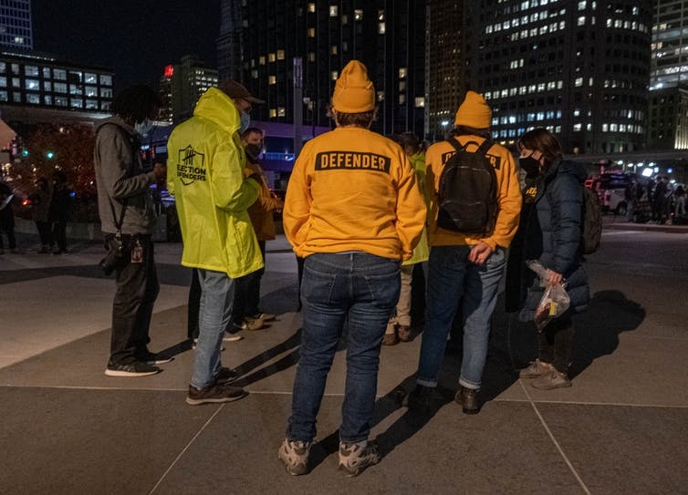 People in orange and yellow sweatshirts labeled 'Defenders' talk in a circle at night