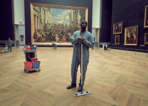 Man cleaning gallery floor.