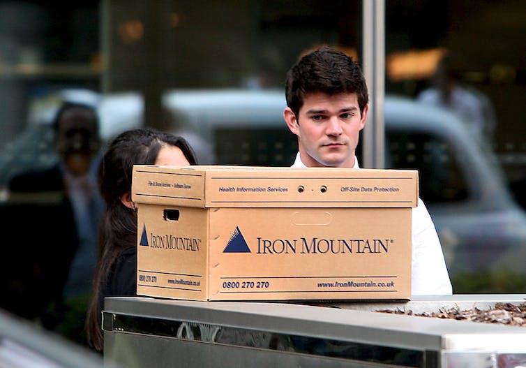 Man looking sad with cardboard box.
