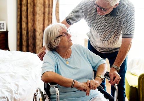 An older man helping an older woman use a wheelchair