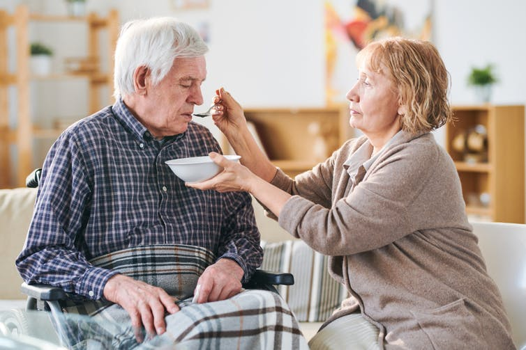 A woman caregiver feeding an older man