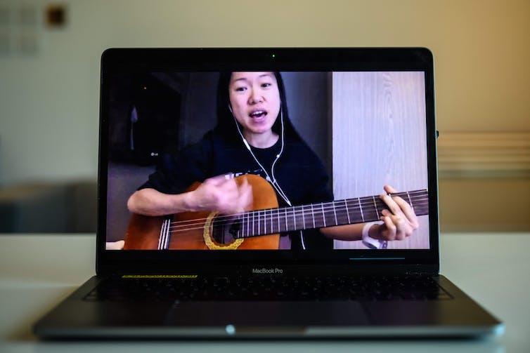 Uma mulher tocando violão nas redes sociais.