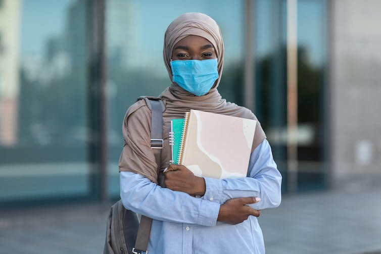 Black muslim female student in mask with workbooks outdoors