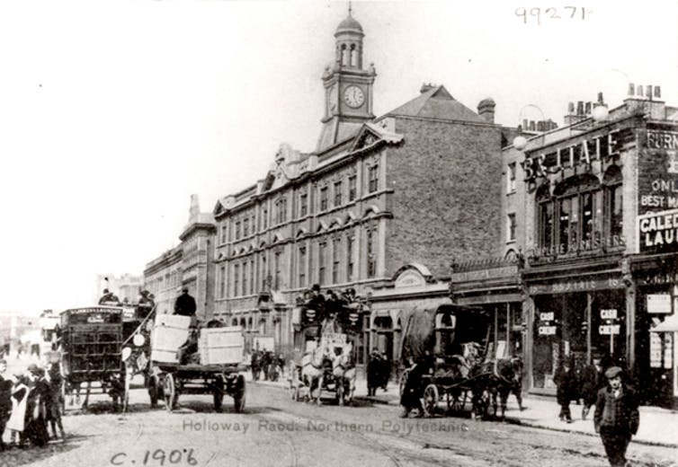Black and white photo of large building with clock tower, with horse-drawn carts and carriages passing in front.