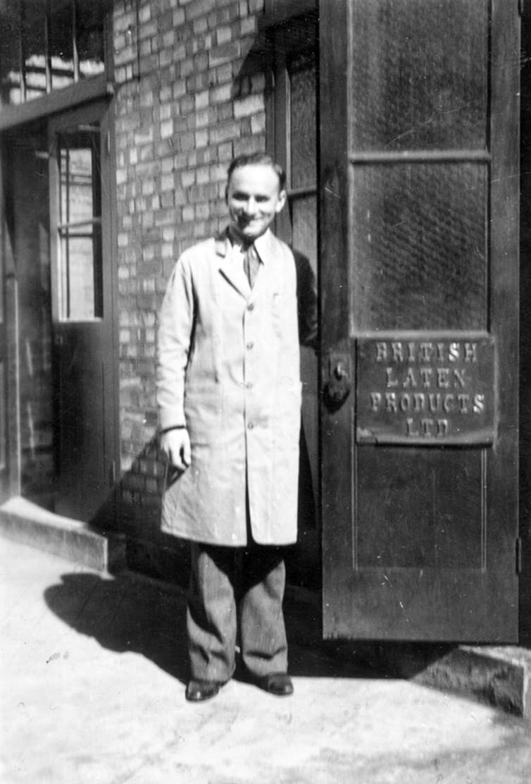 Black and white photo of smiling man in warehouse coat stood outside door with sign for 'British Latex Products'.