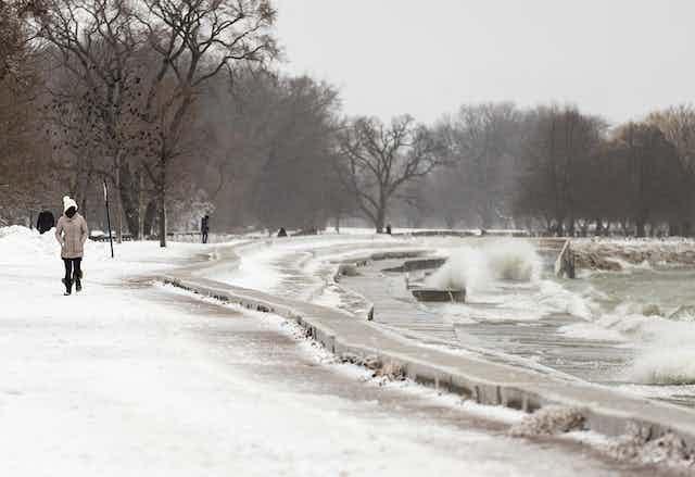 A few people walk in snow near splashing waves