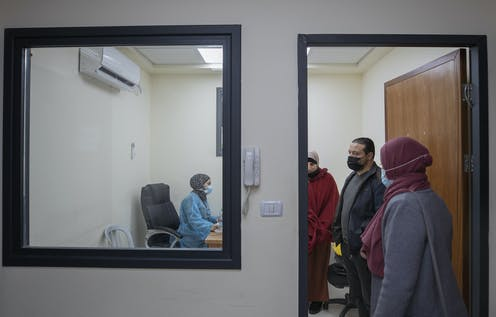 A medical staffer registers Palestinian patients infected with COVID-19 at the emergency unit, in the Palestine Medical Complex, in the West Bank city of Ramallah,