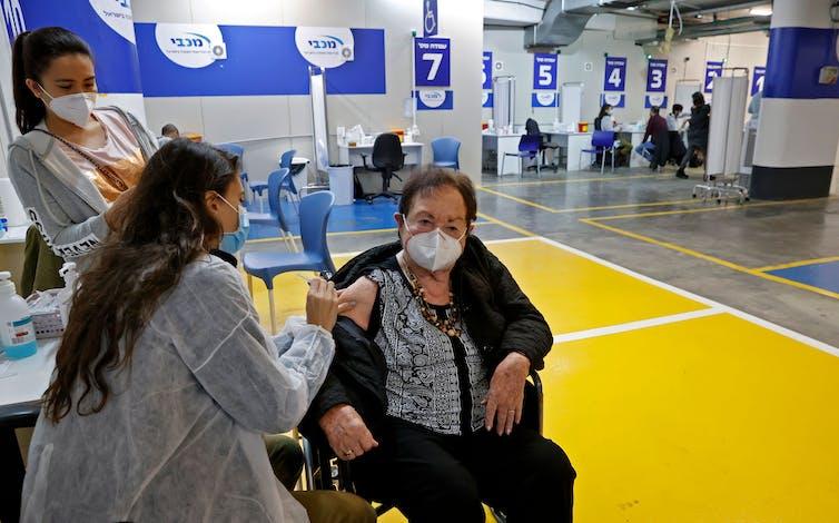 A health worker administers a coronavirus vaccine inside a parking garage in Tel Aviv.