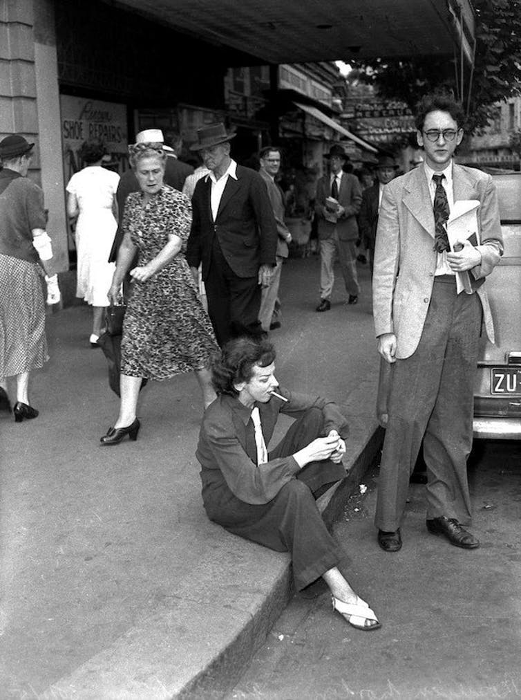 Norton wearing slacks, smoking in public, sitting in the gutter. A woman walks past, looking scandalised.