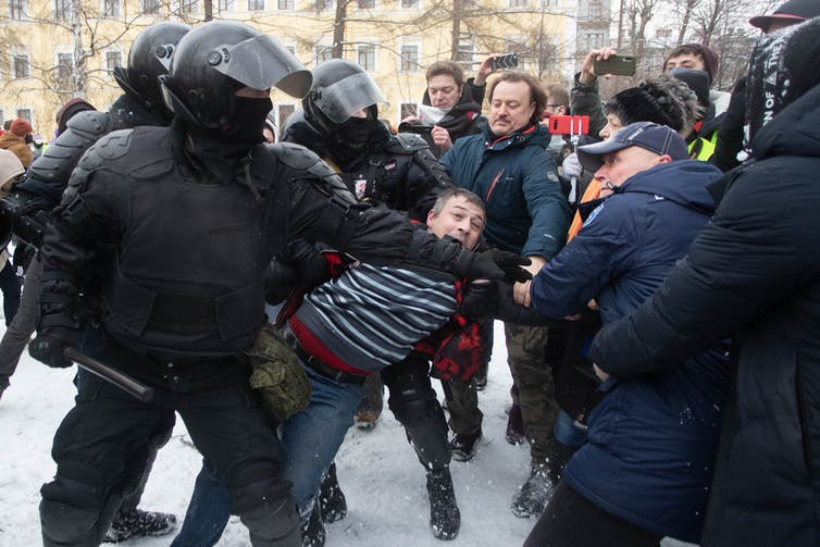 Riot police dragging a protester away in St. Petersburg, Russia.