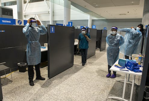 Workers at Pearson Airport put on protective gear