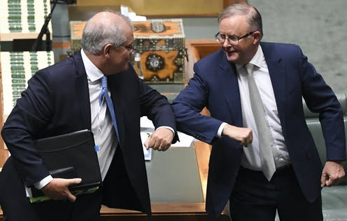 Scott Morrison and Anthony Albanese nudge elbows together in parliament.