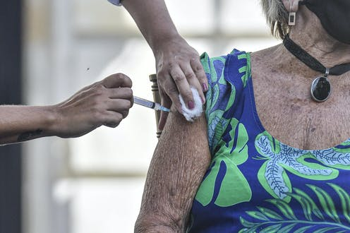 An elderly woman receives the vaccine in Brazil.