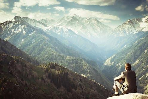 Man in suit looks over mountain vista