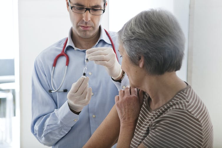 A doctor prepares to vaccinate a grey-haired woman.