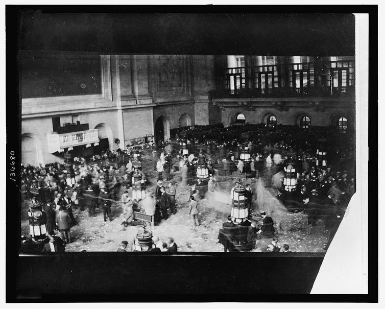 Black and white bustling photo of the floor of the New York Stock Exchange,
