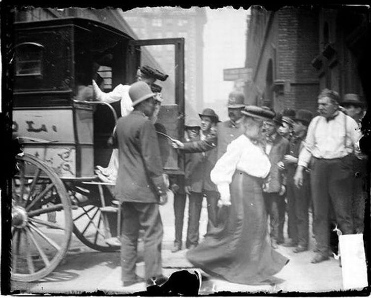 Image of two women exiting a police van past two policemen and a crowd of people watching on the sidewalk.