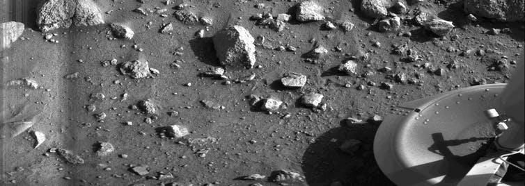A rock strewn field and the foot of the Viking 1 lander appears in one corner.