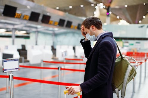 Man in mask, puts his head in hand at empty airport check-in