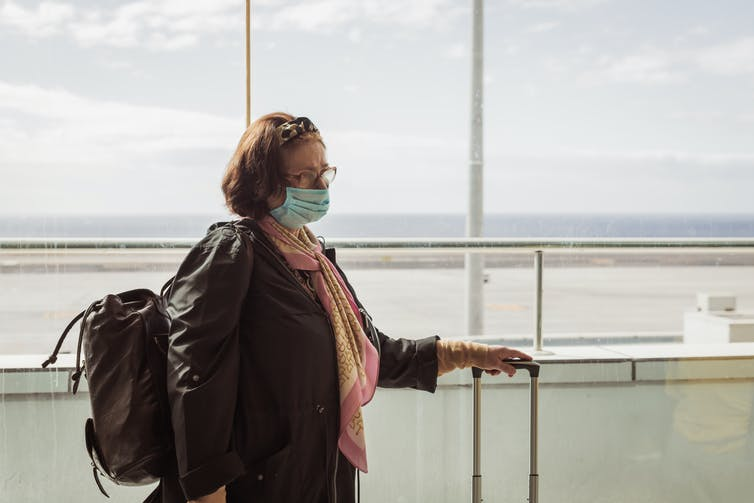 Elderly woman in mask waits at airport.