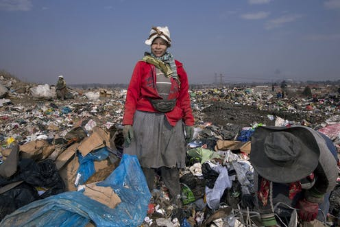 A woman dressed in layers of dirty clothing looks into the camera in a sea of rubbish at a dump.