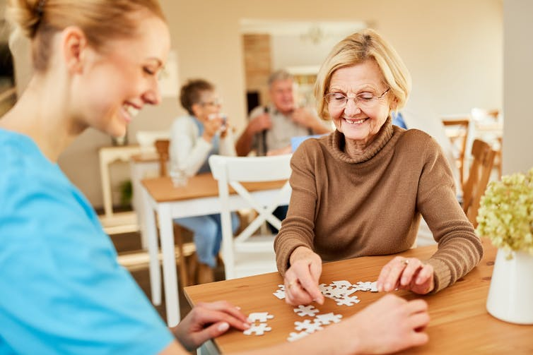 Elderly woman and her nurse completing a puzzle in a care home.