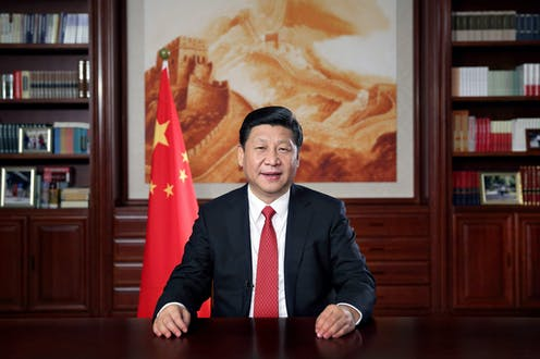 Chinese president Xi Jinping delivers speech from his desk in front of a painting of the Great Wall of China and the national flag.