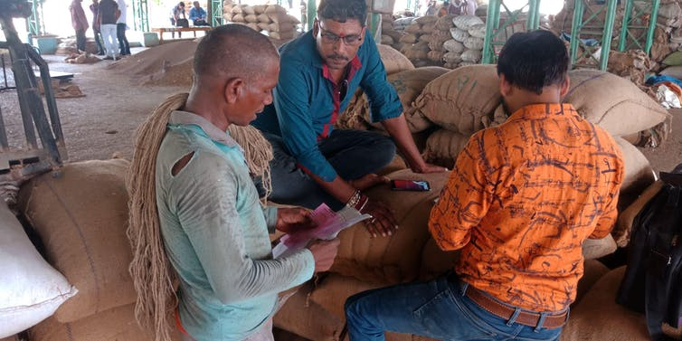 Three farmers make a deal around agricultural sacks in an Indian mandi