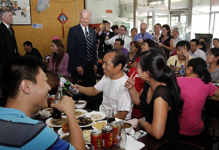 US vice-president Joe Biden walks into a crowded restaurant in China.