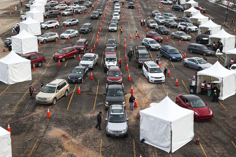 Cars wait in line to stop at vaccination tents.