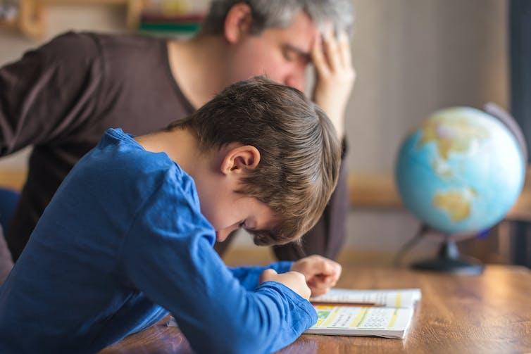 Padre e hijo mirando estresado haciendo los deberes