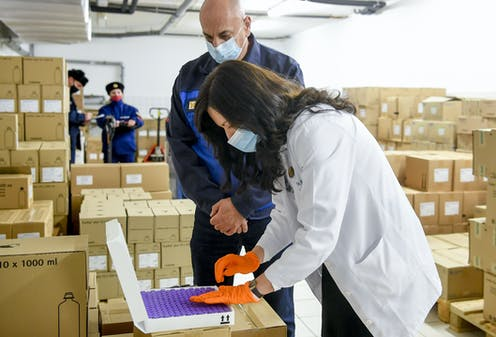 A health worker and delivery person checking a tray of vaccines, surrounded by boxes