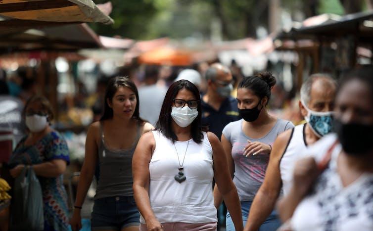 Una mujer con una máscara caminando por una calle en Río de Janeiro, Brasil