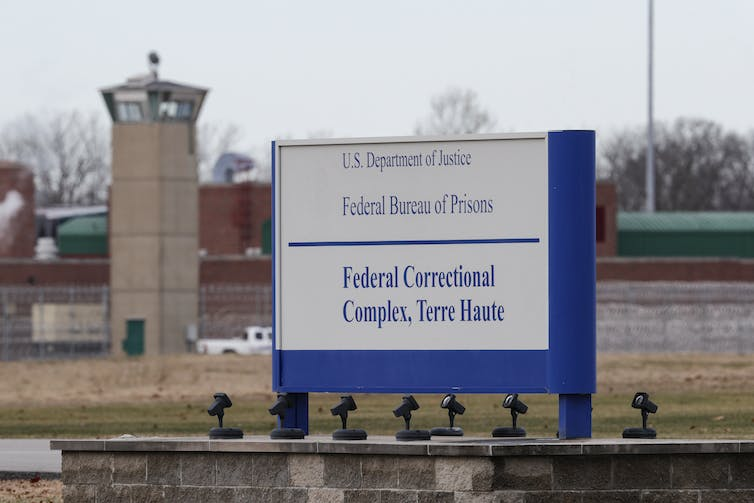 A sign at the prison entrance is shown with a guard tower in the background.