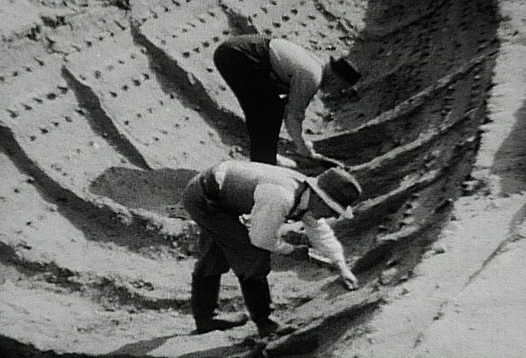 Black and white photo of two men bending over to study ship imprint in the soil.