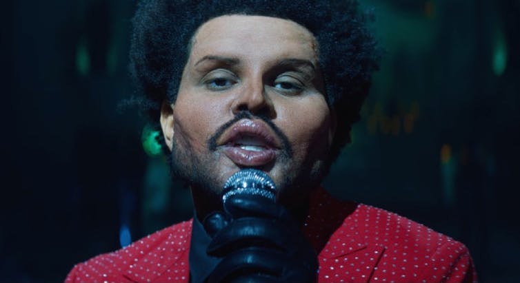 The Weeknd croons, his face swollen with prosthetics.