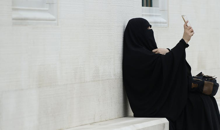 A covered Muslim woman is taking a selfie while seated on a bench