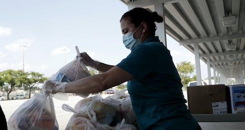 A woman wearing a mask holds plastic bags to give away.