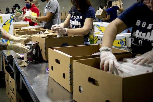 People load food into cardboard cartons