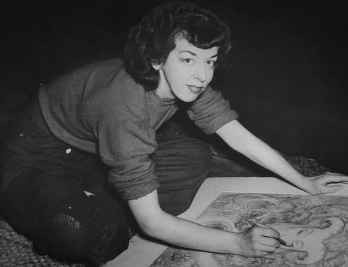 Black and white photo, a woman looks to camera while drawing.