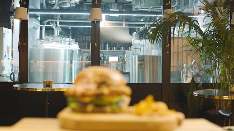 Vista de un plato con carne artificial procedente de células de pollo cultivadas in vitro del restaurante The Chicken con la planta piloto de SuperMeat al fondo. Supermeat