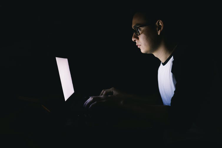 Young man working on his laptop in the dark.
