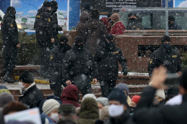 Police wearing face coverings approach a group of protesters.