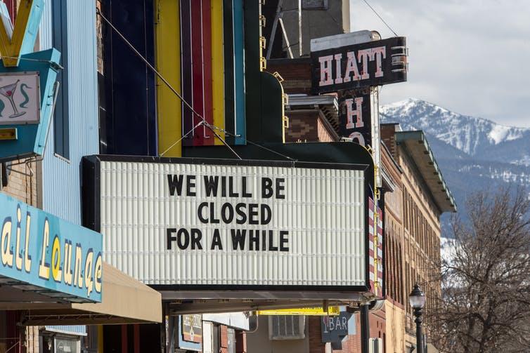 A movie theater displays a sign stating 'we will be closed for a while.'
