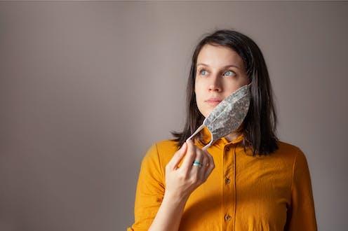 Una mujer se quita la mascarilla mientras mantiene la mirada alta y profunda.