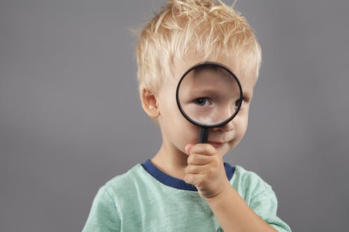 A young boy holds a magnifying glass up to his eye