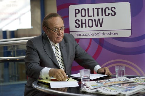 BBC politics broadcaster Andrew Neil sitting at a desk covered in newspapers in front of a sign saying: Politics Show.