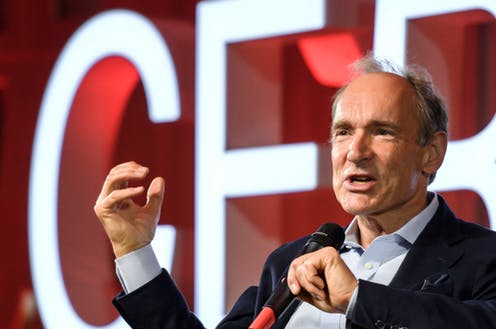 Tim Berners-Lee speaking with a microphone at a CERN meeting