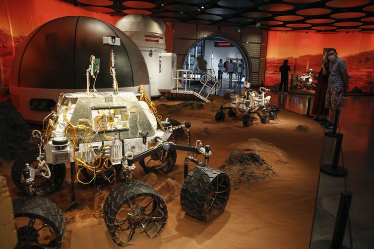 Museum visitors look at a rover replica in a recreated Mars landscape.