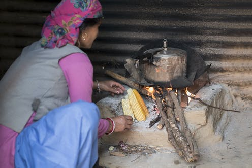 Woman cooking food on wood fire stove.